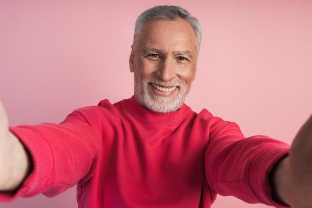 Inquadratura ravvicinata delle mani di un uomo anziano che tiene il suo telefono, prendendo un selfie, su una parete rosa