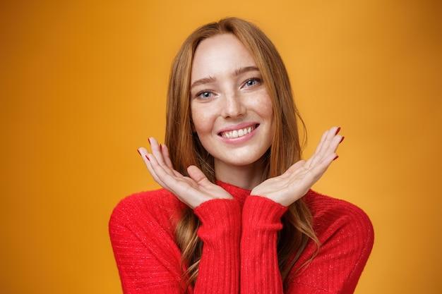 Primo piano di una sensuale ragazza allo zenzero tenera e gentile con romanticismo e sguardo felice che tiene i palmi vicino alla pelle pura e pulita con le lentiggini che sorride gioiosamente inclinando la testa che sembra amichevole sul muro arancione