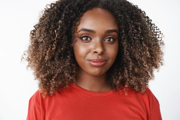 Primo piano di una donna afroamericana sincera, felice e carismatica con acconciatura afro in maglietta casual rossa che sorride e guarda premurosa davanti sentirsi rilassata e paziente sul muro bianco