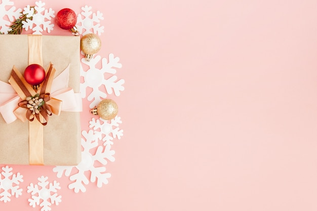 Immagine ravvicinata di piccolo regalo avvolto con nastro su sfondo rosa