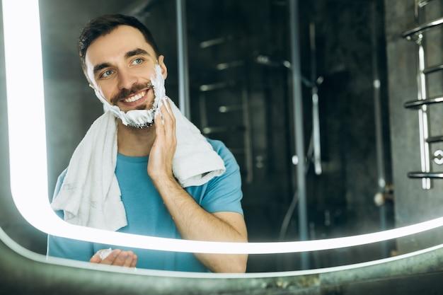 Colpo del primo piano del giovane sorridente con l'asciugamano nel collo in piedi davanti allo specchio e applicando schiuma da barba sul viso.
