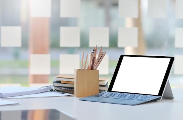 Inquadratura ravvicinata di tablet mockup schermo vuoto sulla scrivania in un comodo ufficio.