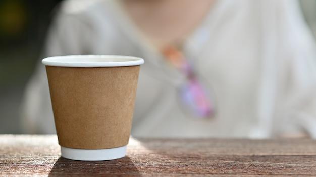 Close-up shot di take away tazza di caffè posto su un tavolo di legno.