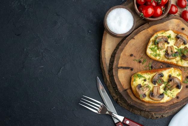Immagine ravvicinata di uno spuntino gustoso con funghi pomodori sale su tavola di legno su sfondo nero