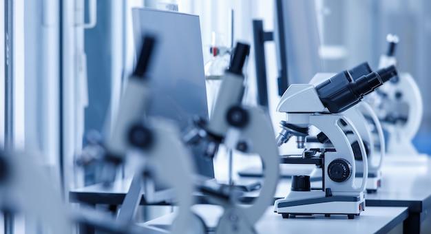 Primo piano di un microscopio scientifico con mirino a due occhi nella fila di una linea di microscopi a un occhio in primo piano sfocato sul tavolo di lavoro del laboratorio utilizzando per il monitoraggio dei campioni di virus coronavirus covid 19.