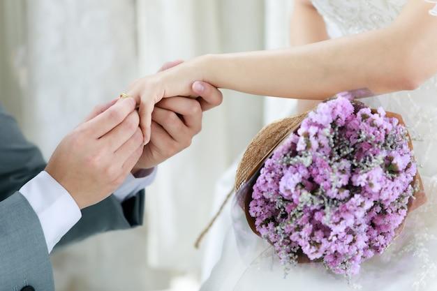 Immagine ravvicinata delle mani irriconoscibili dello sposo in abito formale grigio in ginocchio indossando l'anello di gioielli in oro rosa con diamanti al dito della sposa felice non identificata in abito da sposa bianco che tiene il mazzo di fiori.
