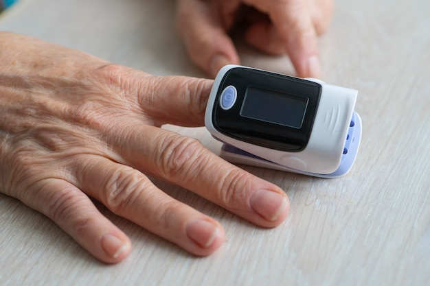 Primo piano utilizzando il pulsossimetro da dito per controllare la saturazione di ossigeno e la frequenza cardiaca di una persona che monitora i sintomi del coronavirus - concetto di epidemia di virus epidemico