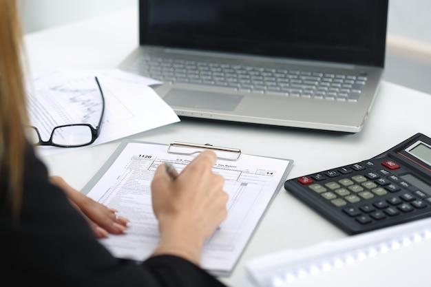 Immagine ravvicinata di donna mano riempimento modulo fiscale. risparmio, finanze e concetto di economia
