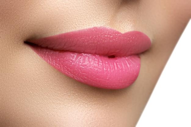 Primo piano sparato di labbra di donna con rossetto rosa. belle labbra perfette