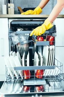 Immagine ravvicinata della mano della donna che estrae i piatti puliti dalla lavastoviglie.