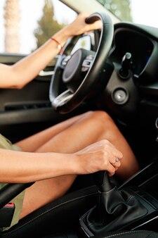 Primo piano delle mani di una donna che guida mentre cambia marcia con la leva del cambio.