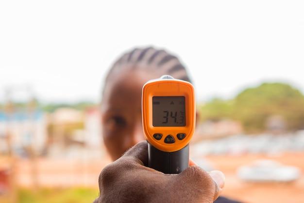 Primo piano di una donna che utilizza un termometro frontale a infrarossi (pistola termometro) per controllare la temperatura corporea per i sintomi del virus - concetto di epidemia di virus epidemico