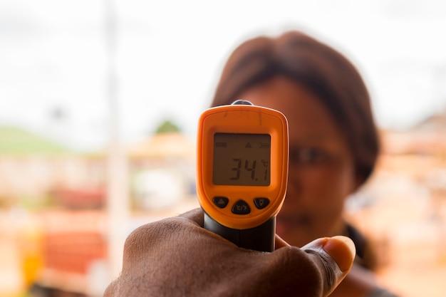 Primo piano di una giovane donna africana che utilizza un termometro frontale a infrarossi (pistola termometro) per controllare la sua temperatura corporea per i sintomi del virus - concetto di epidemia di virus epidemico