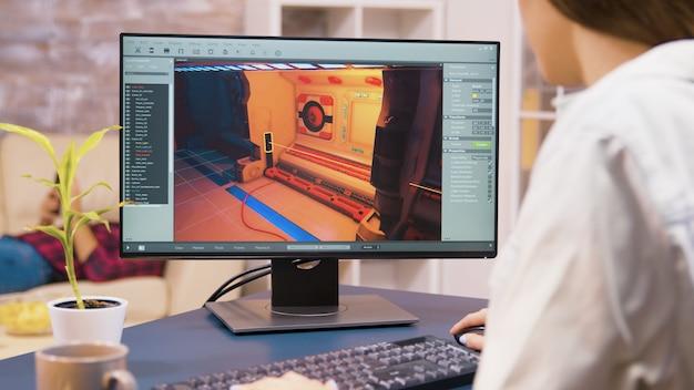 Immagine ravvicinata di una giovane sviluppatrice di giochi che lavora su un nuovo livello di videogiochi in casa sua