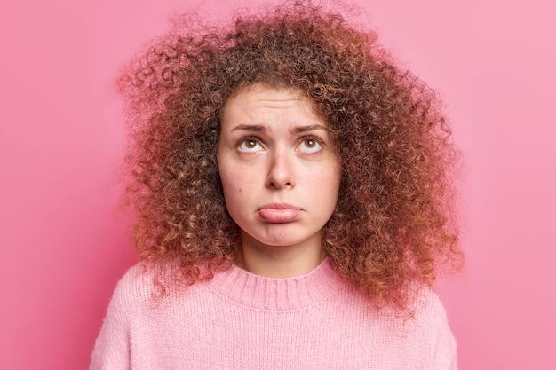 Primo piano shoto di giovane donna triste concentrata sopra le borse il labbro inferiore ha i capelli ricci e folti ha un'espressione insoddisfatta si rammarica di qualcosa vestito con un maglione casual isolato sul muro rosa