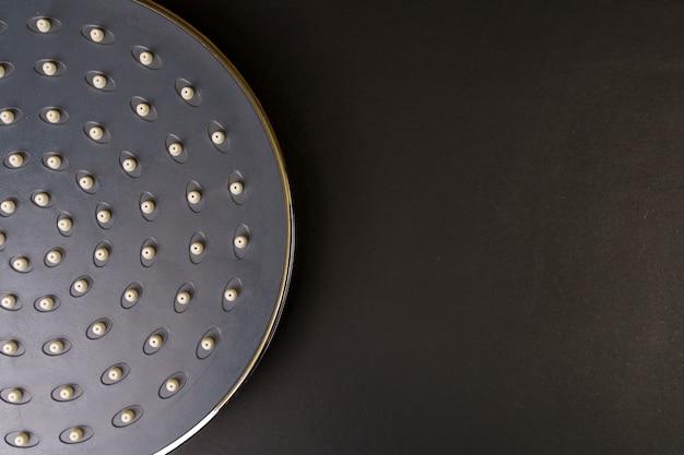 Primo piano di un soffione doccia su sfondo nero. nuova doccia a pioggia grigia. cabina doccia