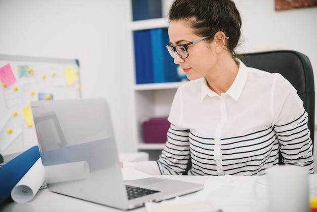 Chiuda sulla vista laterale della donna occupata professionale bella ed elegante che si siede nell'ufficio davanti a un computer portatile.
