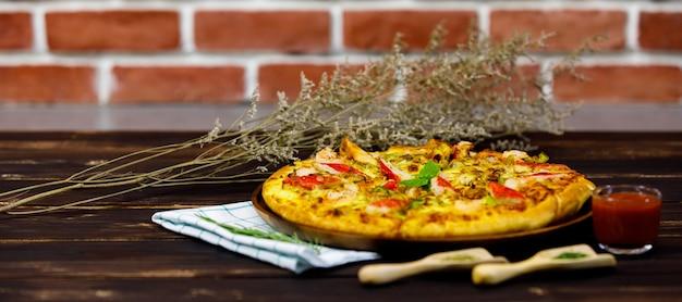 Primo piano vista laterale della gustosa pizza di pesce cotta servita su un tavolo marrone vicino a un muro di mattoni con condimento, bicchiere di ketchup, tovaglie e lusso decorato da fiori secchi per essere un pasto italiano di alta classe