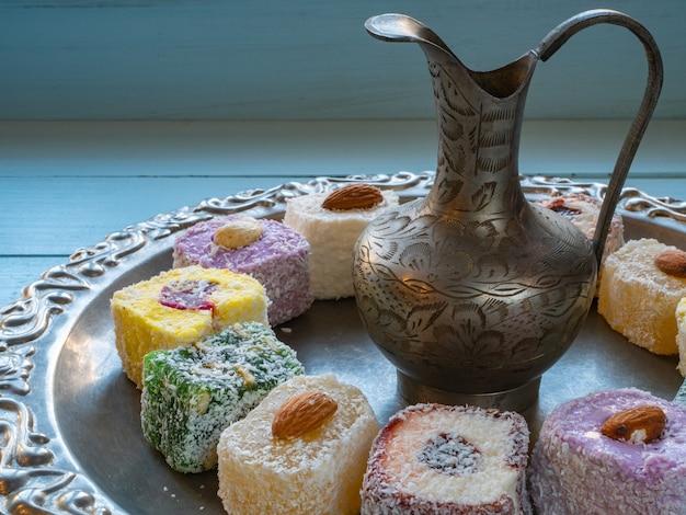 Close up della brocca d'argento con delizie turche caramelle gommose sul vassoio di argenteria