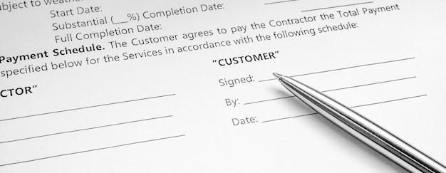 Primo piano di una penna d'argento sul contratto del documento. firma del contratto legale. compra vendita contratto immobiliare.