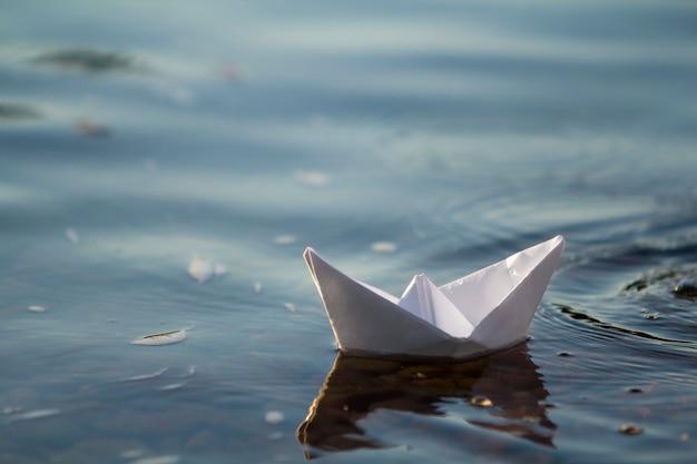 Primo piano di piccola barca bianca semplice della carta di origami che galleggia tranquillamente in chiaro fiume blu o acqua di mare sotto il cielo luminoso di estate. concetto di libertà, sogni e fantasie, sfondo copyspace.