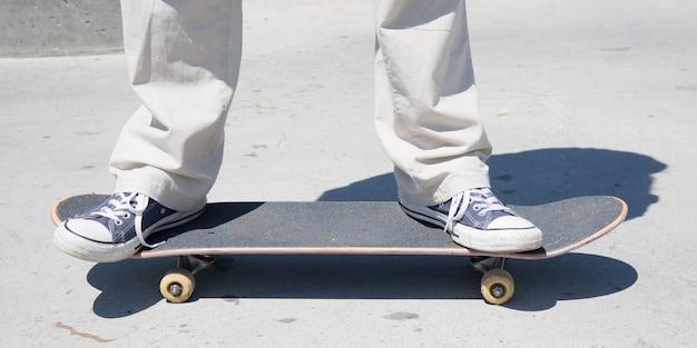 Chiuda su dei piedi di uno skateboarder mentre pattinano sul calcestruzzo allo skate park
