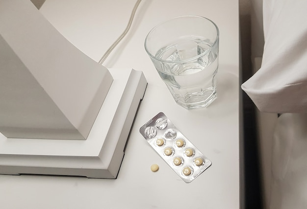 Primo piano di sonniferi e un bicchiere d'acqua preparato per un sonno calmo e sano sul comodino della camera da letto, il concetto di salute e malattia.