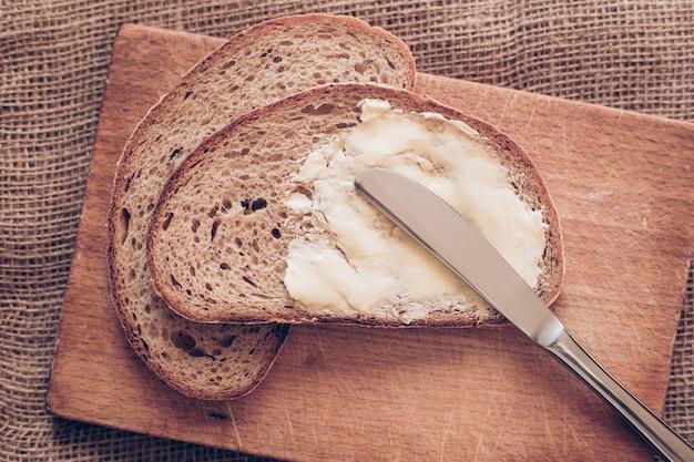 Close-up fetta di pane con burro e coltello sulla scrivania in legno