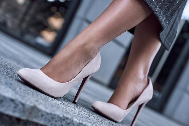 Primo piano di gambe sottili di donna che indossa scarpe con tacco alto