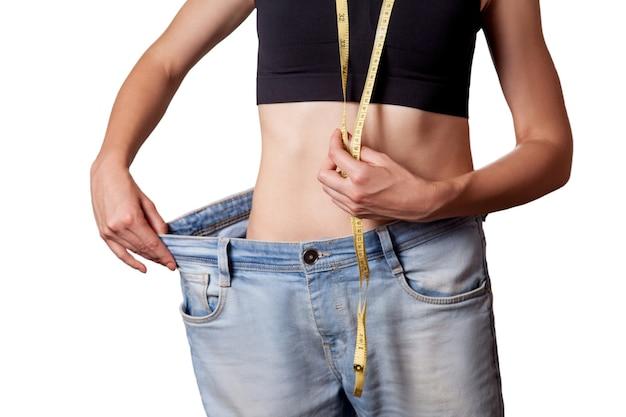 Primo piano della vita sottile della giovane donna in grandi jeans che mostra perdita di peso riuscita, isolata su fondo bianco, concetto di dieta.