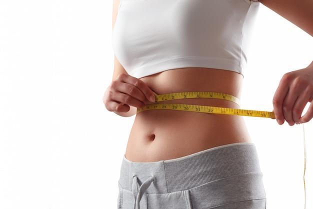 Chiuda in su della donna esile che misura la dimensione della sua vita con la misura di nastro.