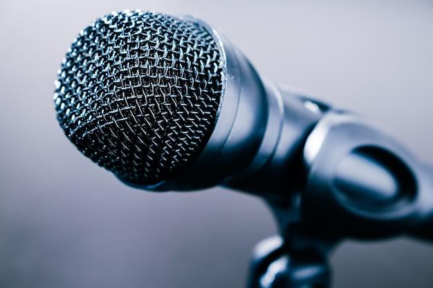 Primo piano del piccolo microfono da scrivania nero con cavo e supporto basso su un tavolo nero. stile moderno, concetto di comunicazione.