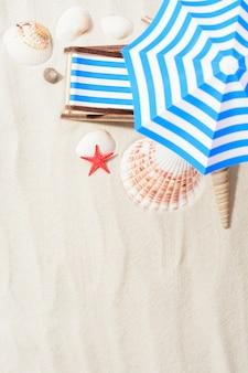 Primo piano di piccolo lettino prendisole e conchiglie di mare a disposizione sulla sabbia