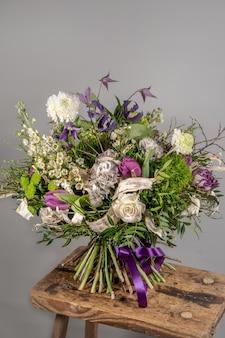 Close-up di piccoli fiori rosa bouquet in vaso di vetro con sfondo grigio sfocato. matrimonio o compleanno, concetto di san valentino.