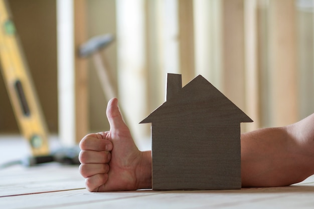 Primo piano di piccola casa di modello di legno sulla mano dell'uomo con il gesto del pollice-su e le immagini vaghe degli strumenti della costruzione. investimenti in proprietà immobiliari e proprietà del concetto di casa dei sogni.