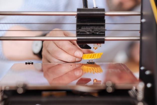 Primo piano di un piccolo modello 3d giallo stampato su una speciale macchina da stampa 3d