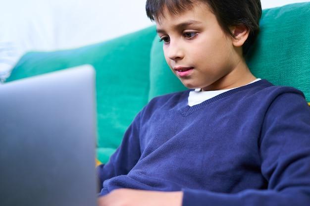 Primo piano di un bambino intelligente e allegro che fa una videoconferenza con un laptop seduto sul divano di casa.