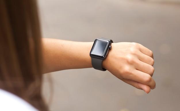 Chiuda in su orologio intelligente sulla mano della donna