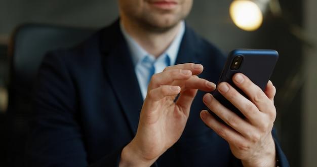Chiuda in su dello smartphone in mano. uomo d'affari che spilla e che scorre sul telefono cellulare in ufficio.