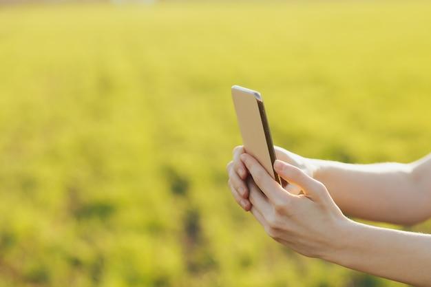 Primo piano di smartphone nelle mani di una ragazza contro il muro di un campo verde.