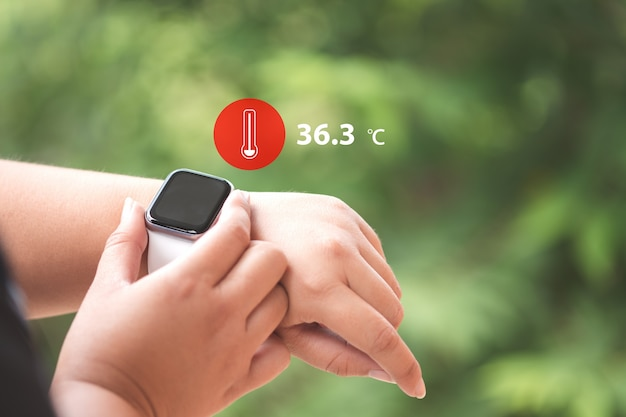 Close up smartwatch con icona misura la temperatura corporea, la tecnologia e il concetto di assistenza sanitaria.