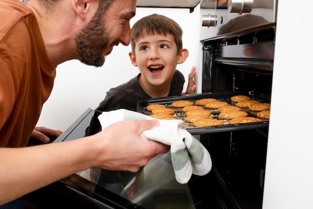 Close up smiley padre e ragazzo cottura