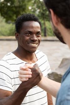 Chiuda in su uomini sorridenti che salutano