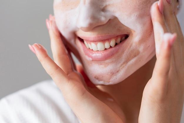 Close up modello di smiley utilizzando il prodotto per il viso