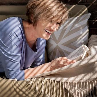 Chiuda sulla lettura della donna di smiley sul divano