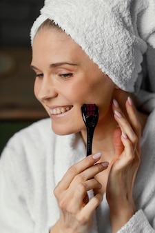 Close up smiley donna utilizzando lo strumento facciale