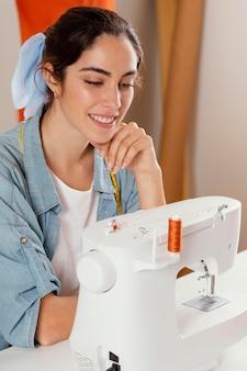 Close-up smiley donna guardando la macchina da cucire