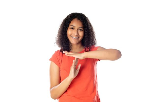 Chiuda in su della donna afroamericana sorridente che indossa la maglietta rossa che sembra isolata.