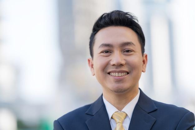 Chiuda in su dell'uomo d'affari asiatico sorridente che sta davanti agli edifici per uffici moderni