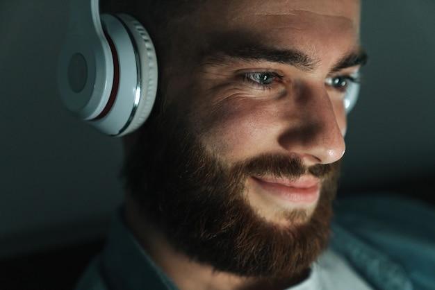 Primo piano di un uomo barbuto sorridente che indossa gli auricolari sdraiato a letto